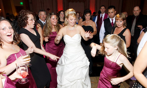 Bride and her guests dance at wedding party