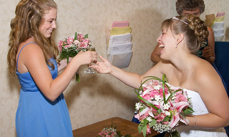 Bride and her bridesmaid share a glass of champagne